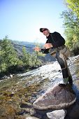 pic of fly rod  - Fly fisherman using flyfishing rod in beautiful river  - JPG