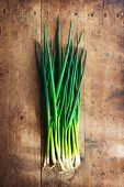 stock photo of scallion  - Fresh harvested bundle of scallions on a old grungy table - JPG