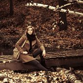 Young fashion woman with handbag in autumn forest