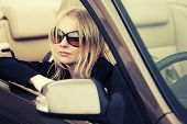 Young fashion blond woman in a convertible car