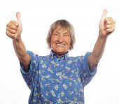 pic of 70-year-old  - Old happy woman showing ok sign on a white background - JPG