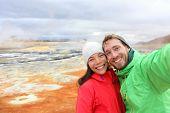 Iceland tourists couple taking selfie photo with smartphone camera at landmark destination: Namafjall Hverarondor hverir mudpot also called mud pool hot spring or fumarole. Beautiful Icelandic nature.