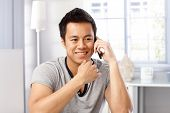 Young man smiling happy, talking on mobilephone, smiling, looking away.