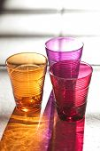 three color drink glasses with reflection on stone background
