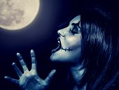 Closeup portrait of terrifying witch yelling in full moon, aggressive woman with spooky makeup screaming in Halloween holiday