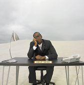 African businessman sitting at help desk in the desert