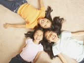 stock photo of three sisters  - Three young Asian sisters lying on the floor with their heads together - JPG