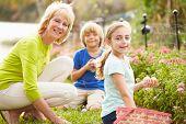 Grandmother With Grandchildren On Easter Egg Hunt In Garden