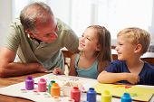 Grandfather Painting Picture With Grandchildren At Home