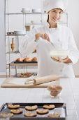 Female pastry chef whisking batter