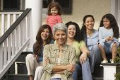 stock photo of niece  - Hispanic grandmother with female family members in the background - JPG
