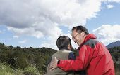 Asian father and son hugging outdoors