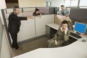 Businesspeople pointing at co-worker in office cubicle