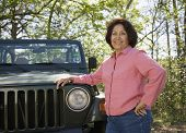 Senior woman leaning on jeep in woods