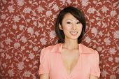 Asian woman smiling in front of floral wallpaper