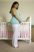 Pregnant Hispanic woman standing next to crib