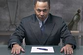African businessman sitting at desk with paper and pen