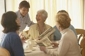 Senior woman talking and laughing with friends