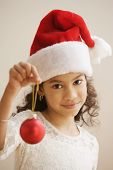 Hispanic girl wearing santa hat and holding Christmas tree ornament