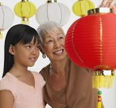 Asian grandmother and granddaughter looking at paper lanterns