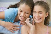 Hispanic sisters using same cell phone