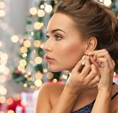 people, holidays and glamour concept - close up of beautiful woman wearing earrings over christmas tree and lights background