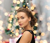 people, holidays, christmas and glamour concept - beautiful woman in evening dress wearing earrings over christmas tree and lights background