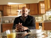happy african man at home at kitchen table portrait