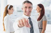 Smiling businessman pointing at camera in the office