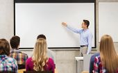 education, high school, teamwork and people concept - smiling teacher standing in front of students and showing something on white board in classroom