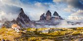 Great foggy view of the National Park Tre Cime di Lavaredo with rifugio Locatelli. Dolomites, South Tyrol. Location Auronzo, Italy, Europe. Dramatic cloudy sky. Beauty world.