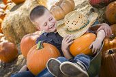 foto of riding-crop  - Two Little Boys Playing in Wheelbarrow at the Pumpkin Patch in a Rustic Country Setting - JPG