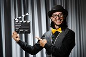 Funny man with movie board against curtain