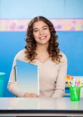 Portrait of beautiful young teacher holding book while sitting at desk in classroom