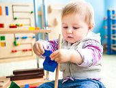 image of playgroup  - cute little girl in the classroom early development plays with numerous  toys - JPG