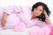 Young pregnant woman lying on plaid with pillows on light background