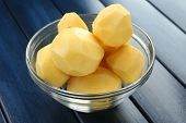 Raw peeled potatoes in glass bowl  on color wooden background