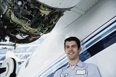 Middle Eastern repairman next to airplane engine