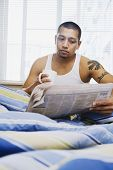 Asian man reading newspaper in bed