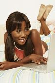 African woman typing on laptop in bed