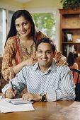 Indian couple paying bills at table