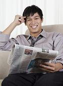 Young Pacific Islander businessman reading newspaper