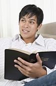 image of pacific islander ethnicity  - Young Pacific Islander man reading - JPG