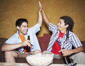 Two Hispanic men high-fiving on sofa