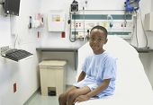 African boy sitting on edge of hospital bed