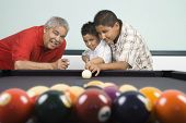 Hispanic grandfather teaching grandsons to play pool