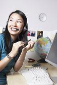 Asian businesswoman filing fingernails at desk