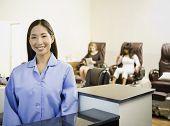 Asian nail technician at counter