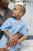 picture of hospital gown  - African boy in hospital gown sitting on father - JPG