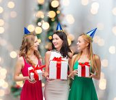 presents, holidays, people and celebration concept - smiling women in party caps with gift boxes over christmas tree lights background